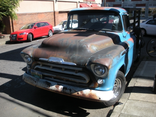 A rusted out, flatbed 1957 Chevy Pickup.